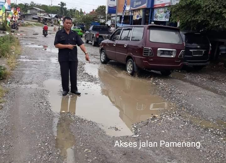 Kerusakan ruas jalan di beberapa titik di Kecamatan Pamenang, Kabupaten Merangin patut jadi perhatian pemerintah. Firdaus Sianturi menunjukkan kerusakan jalan yang digenangi air di Pasar Pamenang, Rabu (28/08/2019) pagi.