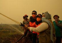 Gubernur dan Bupati pegang langsung slang pemadam saat berada di salah satu titik Karhutla di Kecamatan Kumpeh Ilir, Kabupaten Muaro Jambi, Jumat (20/09/2019) siang. Foto : Hmsprov