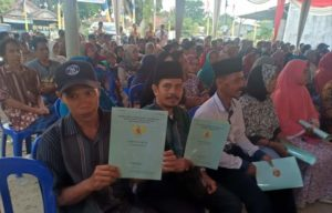 Secara simbolis, sertifikat gratis dibagikan pada warga 2 desa di Bahar Utara. Tampak 2 warga menunjukkan sertifikatnya
