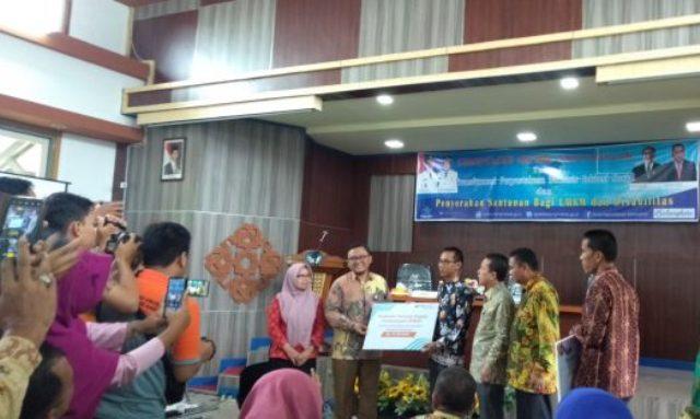 DINAMIKA JAMBI - Bupati Batanghari, Ir H Syahirsyah serahkan santunan pada penyandang disabilitas. Ia mendukung transformasi perpustakaan.